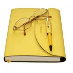 Yellow orgaynizer, glasses and pen on a white background